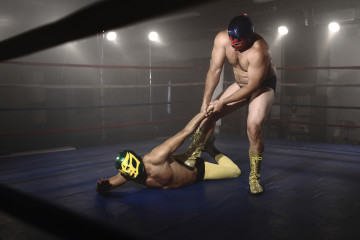 Two masked wrestlers fight in grungy ring