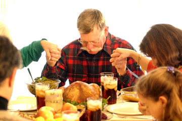 Grandfather saying blessing before eating Thanksgiving Day meal; the entire family is holding hands.